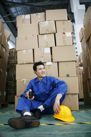 Man in protective work wear listening to music Stock Photo