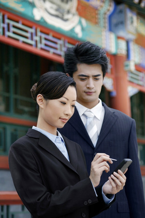 palmtop: Businesswoman using palmtop, businessman watching