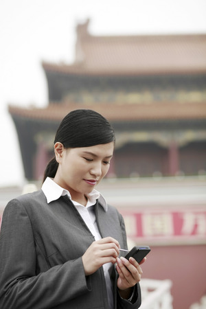 handheld computer: Businesswoman using a personal digital assistant LANG_EVOIMAGES