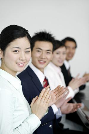 manos aplaudiendo: La gente de negocios sonriendo a la c�mara mientras aplaudiendo manos
