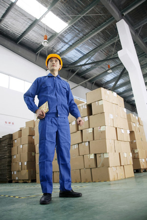Man in protective work wear holding clipboard Stock Photo