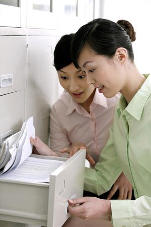 curios: Businesswomen looking through file cabinet LANG_EVOIMAGES