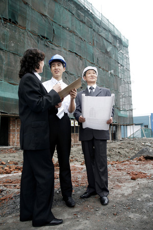 full grown: Business people having discussion at the construction site LANG_EVOIMAGES