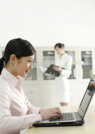 two persons only: Businesswoman using laptop, colleague reading document in the background