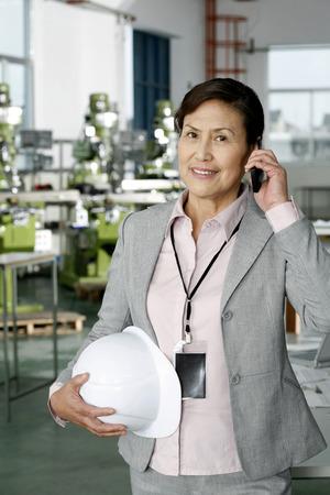 safety helmet: Empresaria con casco de seguridad hablando por tel�fono