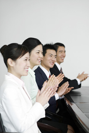 clapping hands: Business people sitting in the board room clapping hands