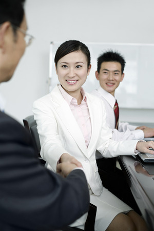 three people only: Handshake between businessman and businesswoman