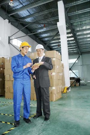 two persons only: Businessman talking to factory worker