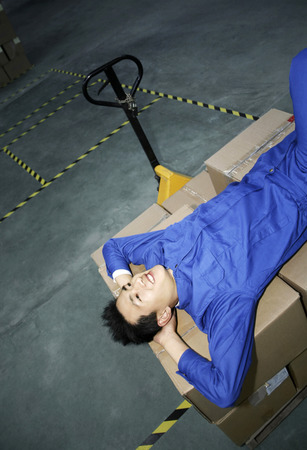 protective wear: Man in protective work wear resting on stacked boxes LANG_EVOIMAGES