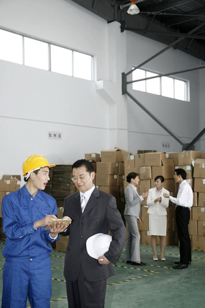 fabrikarbeiter: Businessman talking to factory worker
