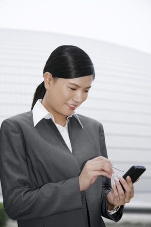 handheld device: Businesswoman using a personal digital assistant LANG_EVOIMAGES