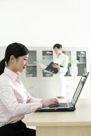 Geschäftsfrau mit Laptop, Kollegen lesen Dokument im Hintergrund