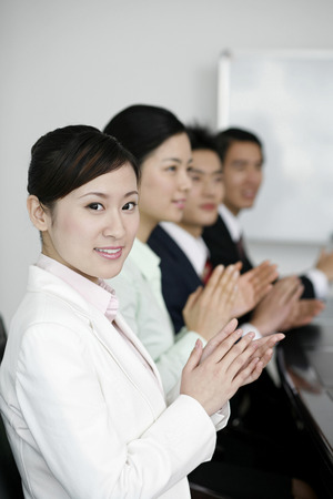 Business people sitting in the board room clapping hands