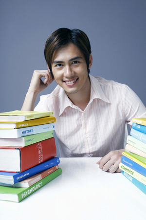 stacked books: Male student with stacked books on the table LANG_EVOIMAGES