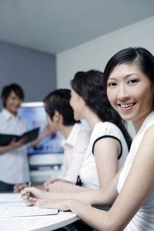 mates: Female student smiling at the camera, course mates paying attention LANG_EVOIMAGES