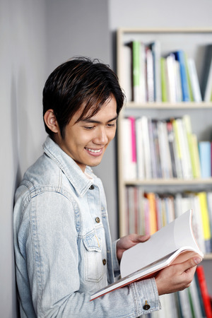 Male student reading book LANG_EVOIMAGES