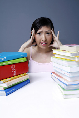 stacked books: Female student with stacked books on the table LANG_EVOIMAGES