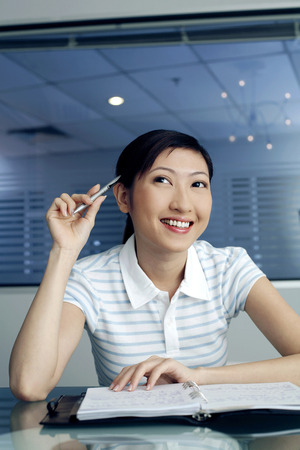 college life: Female student holding pen while thinking LANG_EVOIMAGES