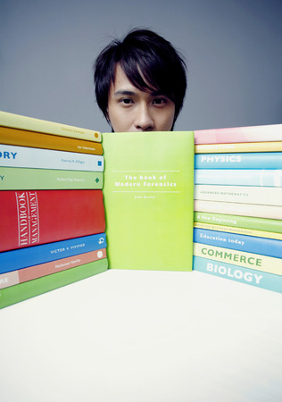stacked books: Male student posing with stacked books