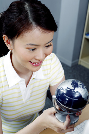 student studying: Female student studying a globe LANG_EVOIMAGES