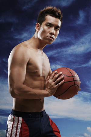 bare chested: Man holding basketball while looking at camera