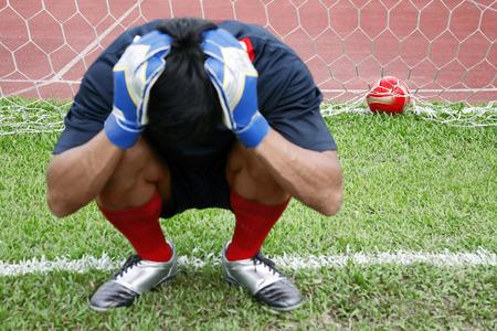 holding on head: Man kneeling in goal holding head in hands