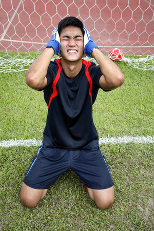 holding the head: Man kneeling in goal holding head in hands