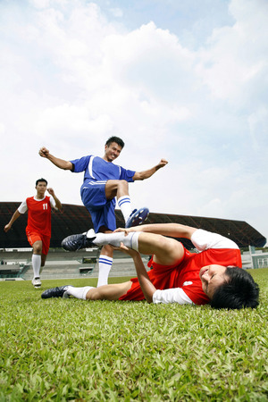Man attacking opponent teams player Stock Photo