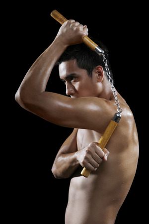 bare chested: Man with nunchaku striking a pose
