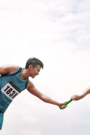 carrera de relevos: Dos manos de los hombres que pasan el testigo en una carrera de relevos LANG_EVOIMAGES