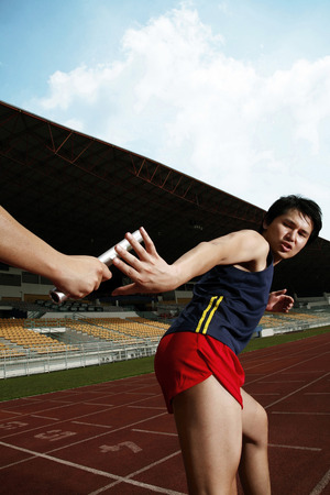 relay baton: Man passing baton to his teammate in a relay event