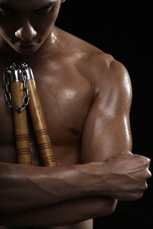 bare chested: Man with nunchaku looking down