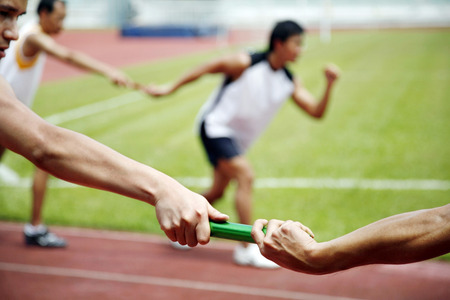 Man passing baton to his teammate in a relay event