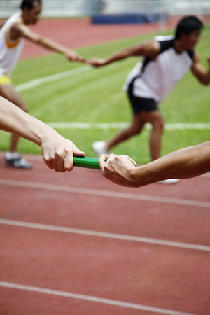 teammate: Man passing baton to his teammate in a relay event