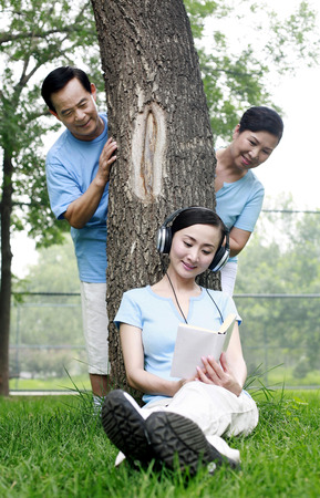 Woman listening to music on the headphones while reading book, senior man and woman peeking from behind the tree