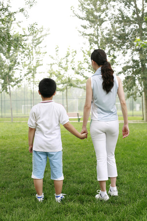 holding hands while walking: Boy and woman holding hands while walking in the park LANG_EVOIMAGES