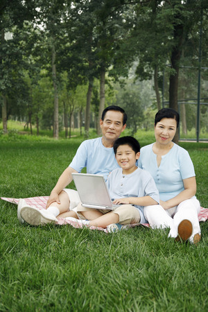 he   my sister: Senior man, senior woman and boy smiling at the camera while using laptop