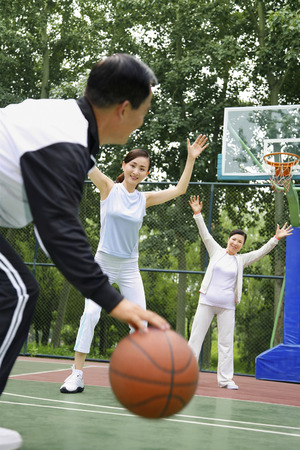 two persons only: Woman playing basketball with senior man and woman