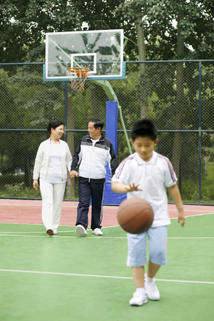 dribbling: Boy dribbling basketball, senior man and woman watching
