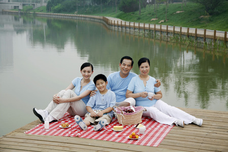 Family picnicking by the lakeside
