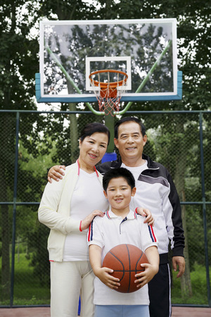 he   my sister: Boy with basketball posing with senior man and woman LANG_EVOIMAGES