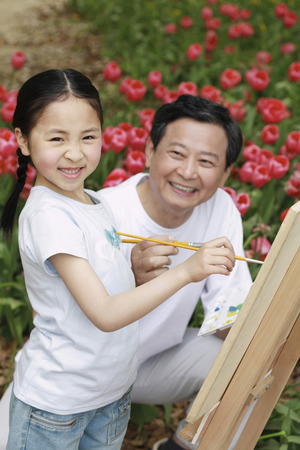 Senior man painting with girl Stock Photo