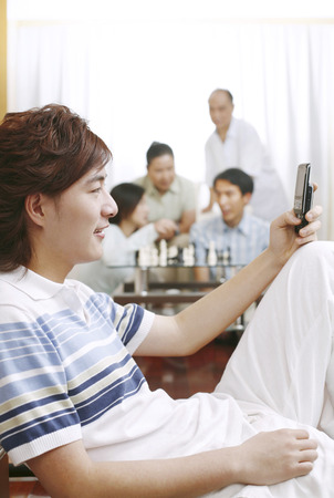 jubilating: Man text messaging on the phone with people playing chess game in the background