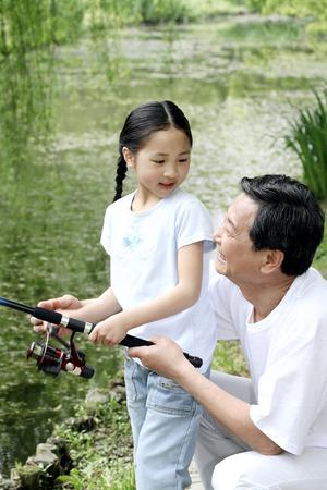 folding arms: Senior man and girl fishing LANG_EVOIMAGES