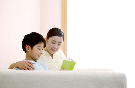 he   my sister: Woman and boy reading book at home