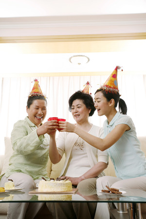 snakes and ladders: Female generations of a family toasting drinks
