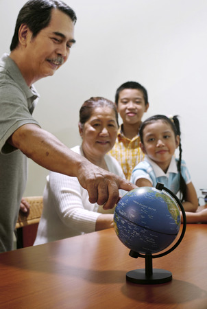 he   my sister: Man showing globe to his family