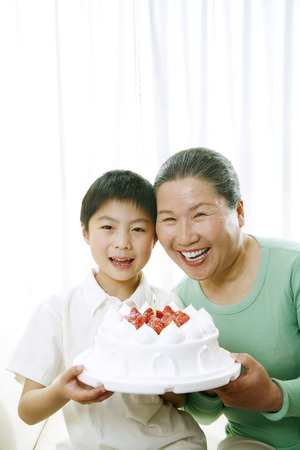 Senior woman and boy with a birthday cake