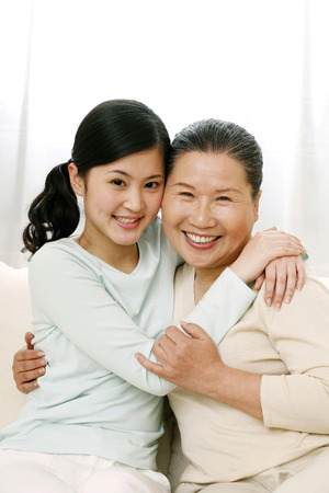 Two women hugging while smiling at the camera
