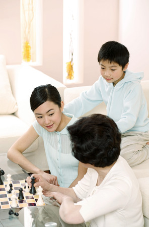 channel surfing: Boy watching women playing chess game at home LANG_EVOIMAGES